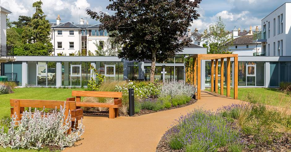 A view of New Court's landscaped grounds showing easy-access paths, two outdoor benches and a wood tunnel.