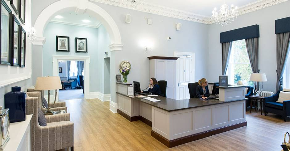 The reception area at New Court where two women are working behind their desks.