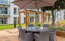 A view of the Grade II listed building from New Courts landscaped grounds showing a table with chairs and umbrella.